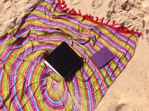 Sarong and journal lying on the sand